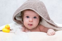 Baby girl under towel in bedroom after bath or shower. Yellow rubber duck and white washcloth lying near her. Textile royalty free stock images