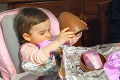 Baby girl unwrap chocolate easter egg newborn.  Royalty Free Stock Images