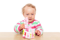 Baby girl unwrapping present. Royalty Free Stock Images