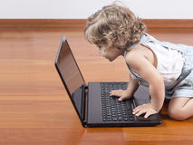 Baby girl using a laptop computer Royalty Free Stock Images