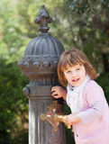 Baby girl using water pump on street of Barcelona stock photos