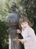 Baby girl using water pump on street of Barcelona stock image