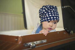 Baby girl in vintage stroller. Beautiful baby looking over the shoulder sitting in a retro stroller Stock Photography