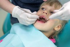 Baby girl visiting stomatology clinic. Dentist making checkup of kids teeth. Children tooth and mouth healthcare