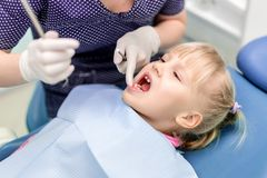 Baby girl visiting stomatology clinic. Dentist making checkup of kids teeth. Children tooth and mouth healthcare.  stock image