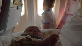 Baby girl traveling by plane with family is waking up. Baby girl waking up after air travel on mother lap. Elder brother looking out plane window stock footage