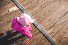 Baby girl walk wood floor pink winter clothes top view Stock Photography