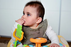 Baby girl  in a walker. Cute baby girl with hand in the mouth  playing in her walker Royalty Free Stock Photos