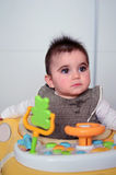Baby girl  in a walker. Cute baby girl playing in her walker Royalty Free Stock Image