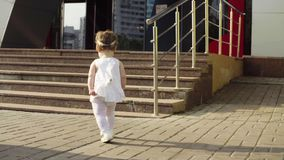 Baby girl walking along the stone road. Near the shopping center early in the morning Royalty Free Stock Images