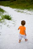 Baby girl walking away on sand Stock Images