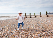 A baby girl walking on the beach holding pebbles Royalty Free Stock Images