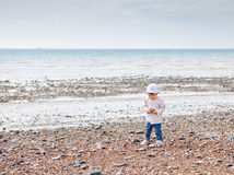 A baby girl walking on the beach holding pebbles Stock Image