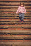 Baby girl walking down. Cute baby girl walking down the stairs in the park Stock Image