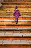 Baby girl walking down old stairs Stock Images