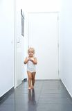 Baby girl walking in hallway at home Stock Images
