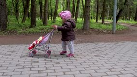 Baby girl walking with her stroller toy in spring park.