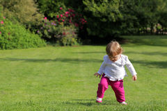Baby girl walking in the park. On a sunny spring afternoon Stock Photos