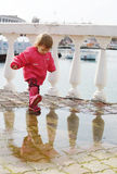 Baby girl walking in puddle Stock Photography