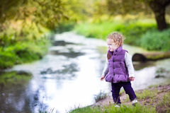 Baby girl walking on a river shore on autumn day Royalty Free Stock Images