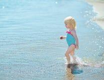 Baby girl walking into sea Stock Photos