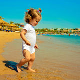 Baby girl walking on the sea water Royalty Free Stock Photography