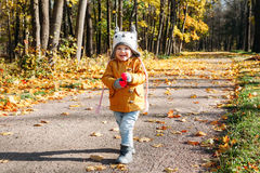 Baby girl walking smiling in the autumn park Stock Image