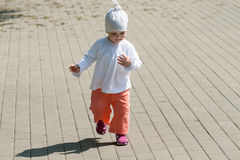 Baby girl walking on the street Stock Image