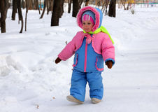 Baby girl walking in winter park Royalty Free Stock Image