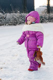Baby girl walking on winter snow street. Stock Images