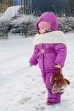 Baby girl walking on winter snow street. Stock Photos