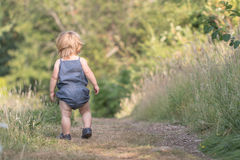 Baby girl walks away on green forest path Stock Photo