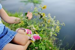Baby girl walks on a river wreath of wild flowers. Child girl lets on the river a wreath of wild flowers. Celebration of Ivan Kupala. Midsummer day Stock Image