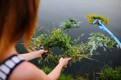 Baby girl walks on a river wreath of wild flowers. Child girl lets on the river a wreath of wild flowers. Celebration of Ivan Kupala. Midsummer day Royalty Free Stock Images