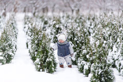 Baby girl in warm snowsuit walking in the winter park with a white snow. Royalty Free Stock Photography