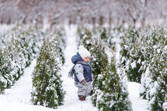 Baby girl in warm snowsuit walking in the winter park with a white snow. Stock Photo