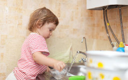 Baby girl  washes dishes Stock Images