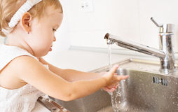 Baby girl washes her hands in the bathroom Stock Images