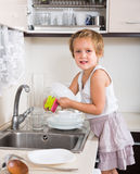 Baby girl washing dishes Royalty Free Stock Image