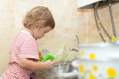 Baby girl washing dishes Royalty Free Stock Photo