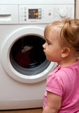 Baby girl and washing machine. Rear view of cute young girl with washing machine in background Stock Photo