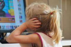 Baby girl watching cartoons. Blond little girl watching cartoons on the Internet stock photo