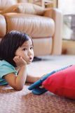 Baby girl watching television while holding tablet Royalty Free Stock Image