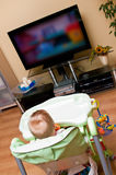 Baby girl watching tv. Baby girl sitting in high chair watching tv (television Royalty Free Stock Image