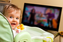 Baby girl watching tv Stock Photos