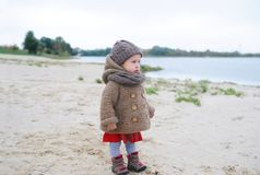 Baby girl watching at water, lake or river, serious face, cold season, autumn. Warm clothes Royalty Free Stock Images
