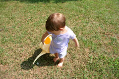 Baby Girl Watering. Adorable baby girl watering lawn. Shot with a Canon 20D stock image