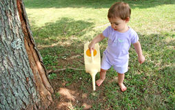 Baby Girl Watering Lawn. Close-up of a cute baby girl watering lawn. Shot with a Canon 20D stock photos