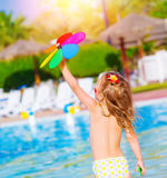 Baby girl in waterpark. Little baby girl having fun in waterpark, sweet child play with colorful flower toy, enjoying summer holiday, resting near poolside Stock Photos
