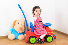 Baby girl waving goodbye on a toy car Stock Images
